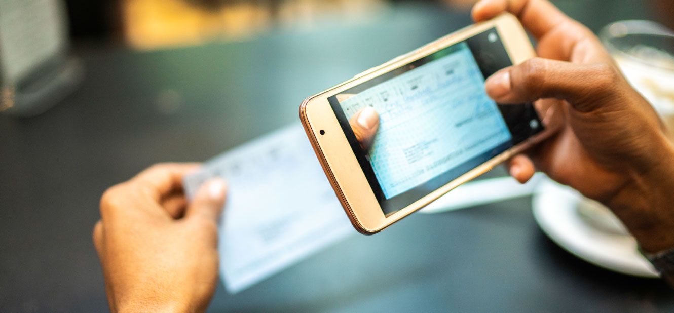 Close up of a person's hands taking a picture of a check with a smartphone