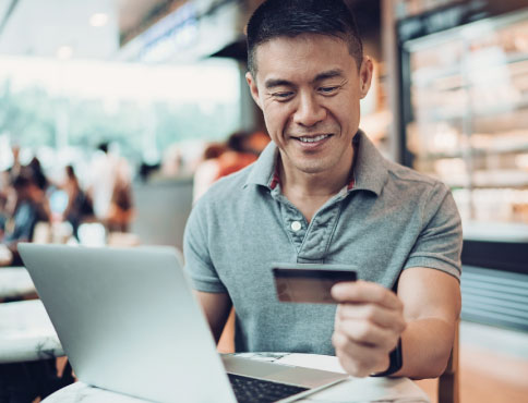 A man sitting down at a laptop with a credit card in one hand
