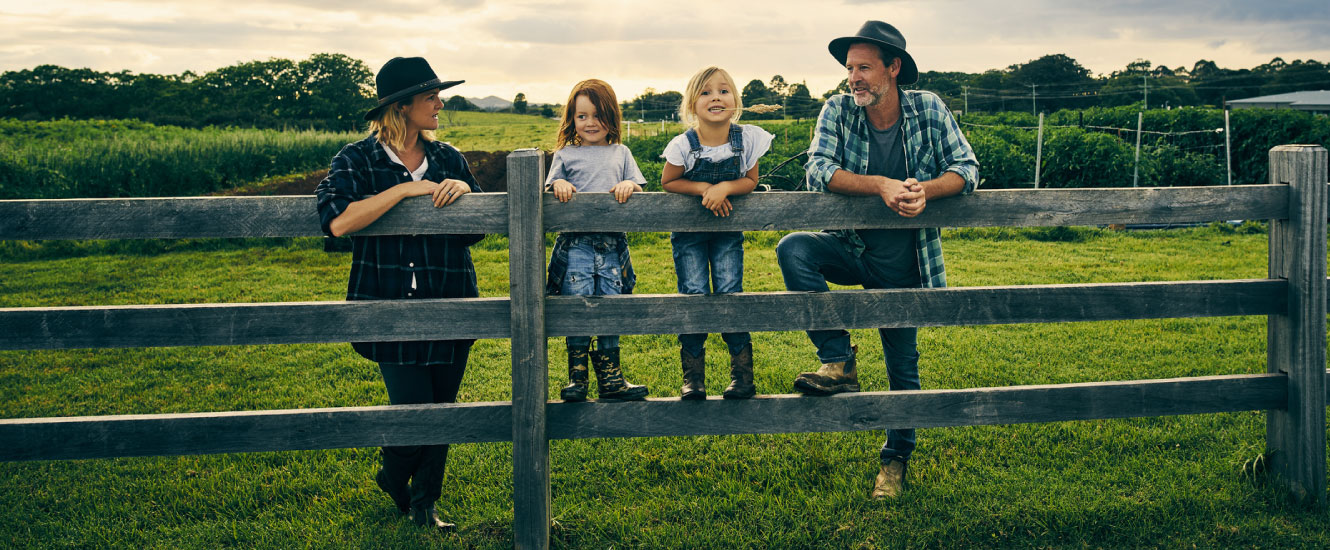 A young rural family leaning against a wooden fence in a large field